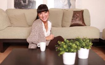 glckliche Frau sitzt in ihrem Wohnzimmer