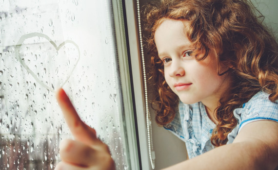 Happy child drawing heart on the window